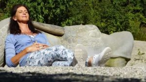 woman laying down on a bench relaxing and breathing